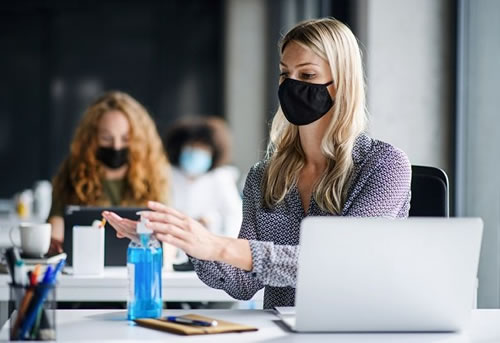 female employee with mask in office covid-19